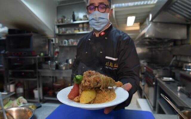 Tunisian chef Taieb Bouhadra presents a prepared traditional Tunisian lamb couscous dish at a restaurant in the Medina (old town) of Tunisia's capital Tunis on December 16, 2020.  (Fethi Belaid / AFP)