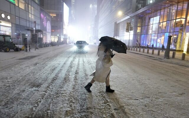 A person holds an umbrella as she walks under the snow in Times Square in New York City, December 16, 2020, as Storm Gail hits the East coast. (Timothy A. Clary/AFP)