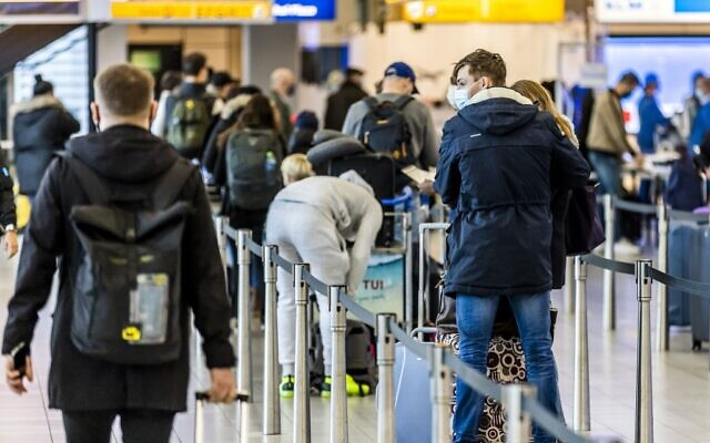 Travelers stand in the departure hall of Schiphol Airport in Amsterdam on December 17, 2020. (Remko de Waal / ANP / AFP)