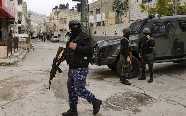Palestinian Authority security forces in balaclavas stand by an armored vehicle at the entrance to Balata camp, near the West Bank city of Nablus, on December 15, 2020.  (Photo by JAAFAR ASHTIYEH / AFP)