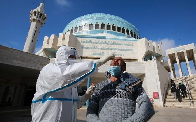 A member of the Jordanian health ministry's epidemiological investigation team takes a random nasal swab to test for coronavirus, from a man leaving the King Abdullah I mosque following the Friday noon prayers, in the capital Amman, on December 18, 2020. (Khalil MAZRAAWI / AFP)