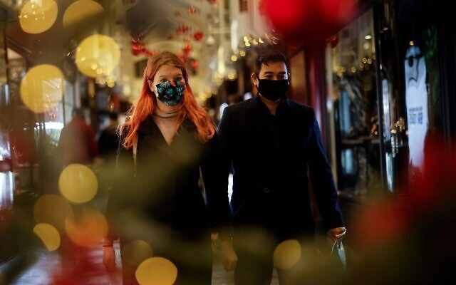 Shoppers, some wearing a face mask or covering due to the COVID-19 pandemic, look at shop window displays inside a christmas-themed Burlington Arcade in London on December 19, 2020. (Tolga Akmen / AFP)