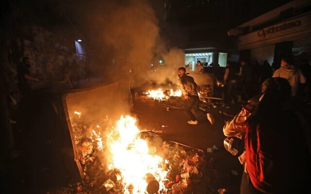 Lebanese students burn dumpsters while protesting a decision by top universities to adopt a new dollar exchange rate to price tuition in Beirut's Hamra district on December 19, 2020 (ANWAR AMRO / AFP)