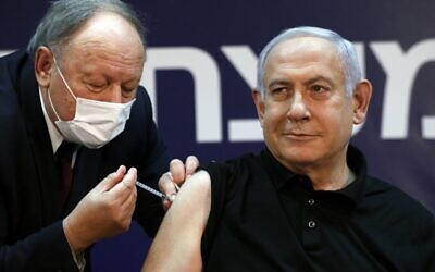 Prime Minister Benjamin Netanyahu receives a coronavirus vaccine, from his personal physician Dr. Tzvi Berkovitz, at Sheba Medical Center in Ramat Gan, on December 19, 2020, becoming the first Israeli to get the vaccine. (Amir Cohen/Pool/AFP)