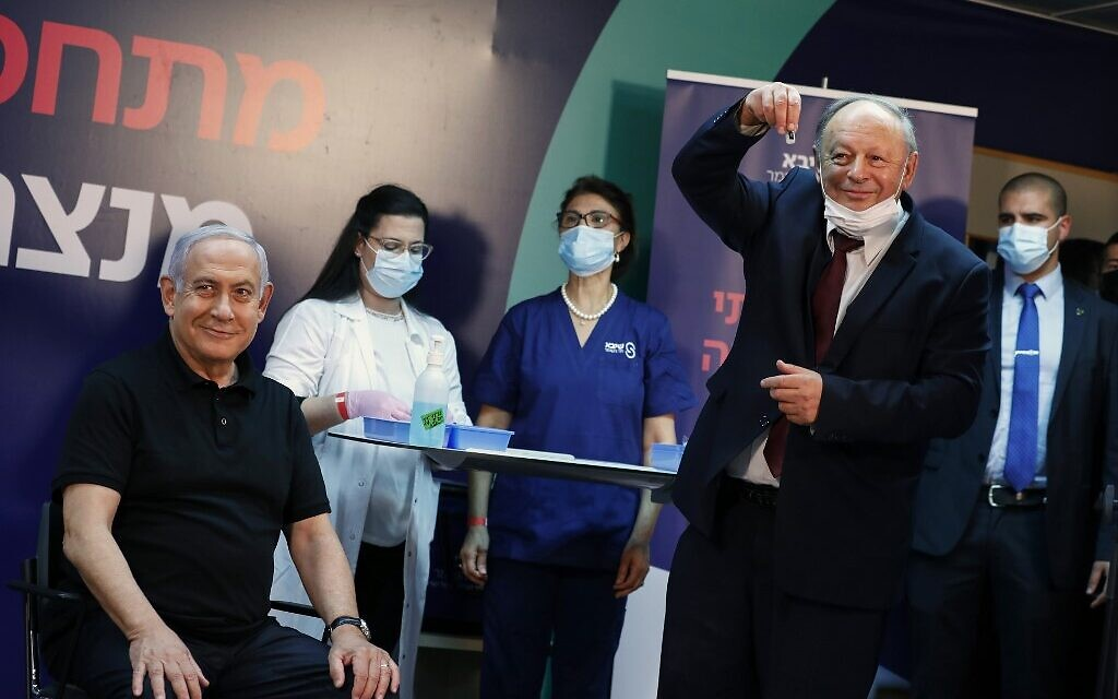 Prime Minister Benjamin Netanyahu smiles before receiving a coronavirus vaccine at Sheba Medical Center in Ramat Gan from his personal physician, Dr. Tzvi Berkovitz. Netanyahu, 71, followed by Health Minister Yuli Edelstein, became the first Israelis to get the vaccine. (AMIR COHEN / POOL / AFP)