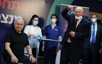Prime Minister Benjamin Netanyahu (L) smiles before receiving a coronavirus vaccine, from his personal physician Dr. Tzvi Berkovitz, at Sheba Medical Center in Ramat Gan on December 19, 2020. At center in background (in blue scrubs) is nurse Shoshi Gomel (Amir Cohen/Pool/AFP)