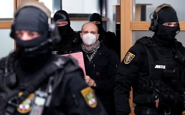 Stephan Balliet (C), who shot dead two people after an attempt to storm a synagogue in Halle an der Saale, eastern Germany, wears a face mask as he arrives for the start of the 26th day of the trial on December 21, 2020, at the district court in Magdeburg, eastern Germany (Ronny Hartmann/ AFP)