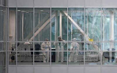 Medical workers are seen in a passageway between the buildings of a hospital in Kommunarka, where patients suffering from the coronavirus disease are treated, on the outskirts of Moscow on December 25, 2020. (NATALIA KOLESNIKOVA / AFP)