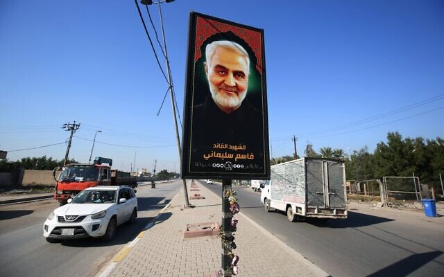 Iraqis drive past a poster depicting late Iranian Revolutionary Guards commander Qasem Soleimani in Iraq's capital Baghdad, on December 30, 2020, ahead of the first anniversary of his killing in a US drone attack. (Ahmad Al-Rubaye / AFP)