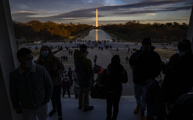 Visitors look out from the Lincoln Memorial across the Reflecting Pool at the Washington Monument as the sun sets on December 26, 2020 in Washington, DC. (Samuel Corum/Getty Images/AFP)