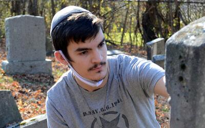 Netanel Crispe works on a headstone at the oldest Jewish cemetery in Vermont. (David LaChance/Bennington Banner/ via JTA)