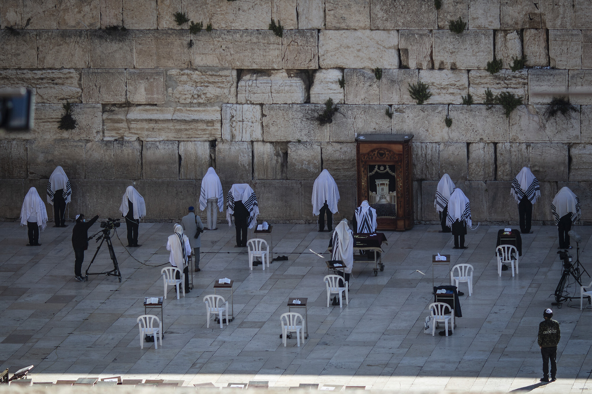 A small group of distanced Jewish priests take part in the traditional Cohanim prayer (priestly blessing), during the Passover holiday at the Western Wall in the Old City of Jerusalem, April 12, 2020. (Photo by Ilia Yefimovich/picture alliance via Getty Images/ via JTA/SUE)