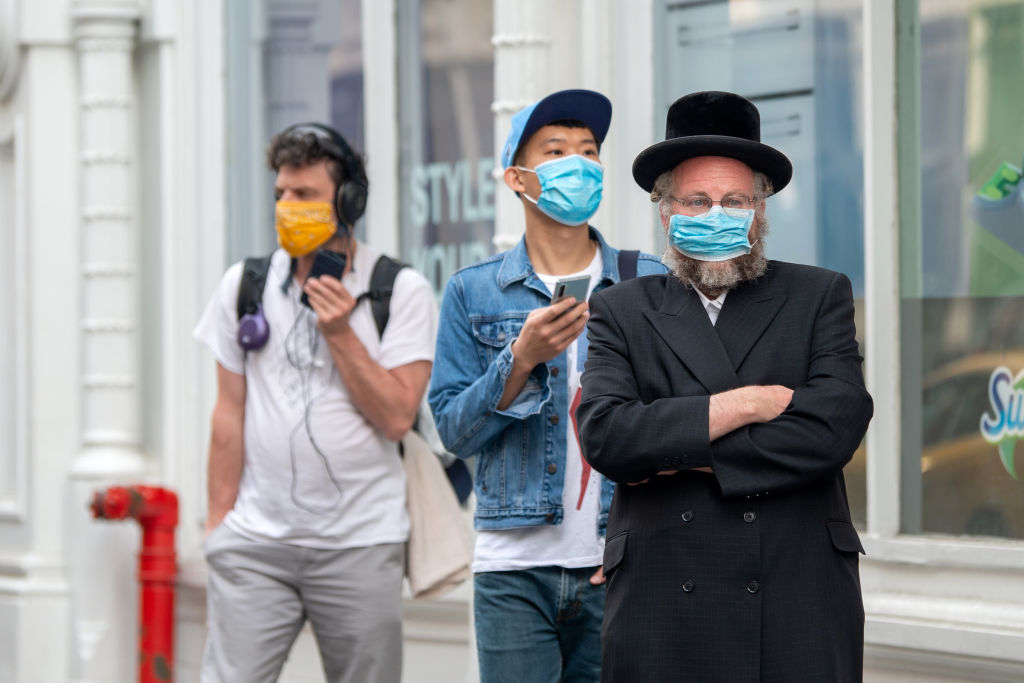People wearing masks wait in line amid the coronavirus pandemic on May 18, 2020 in New York City. (Photo by Alexi Rosenfeld/Getty Images/ via JTA/SUE)
