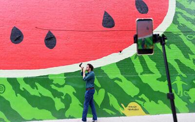 Rabbi Aaron Potek blows a shofar while recording a TikTok video in front of a watermelon mural on September 9, 2020 in Washington, DC. (Photo by Matt McClain/The Washington Post via Getty Images/ via JTA/SUE)