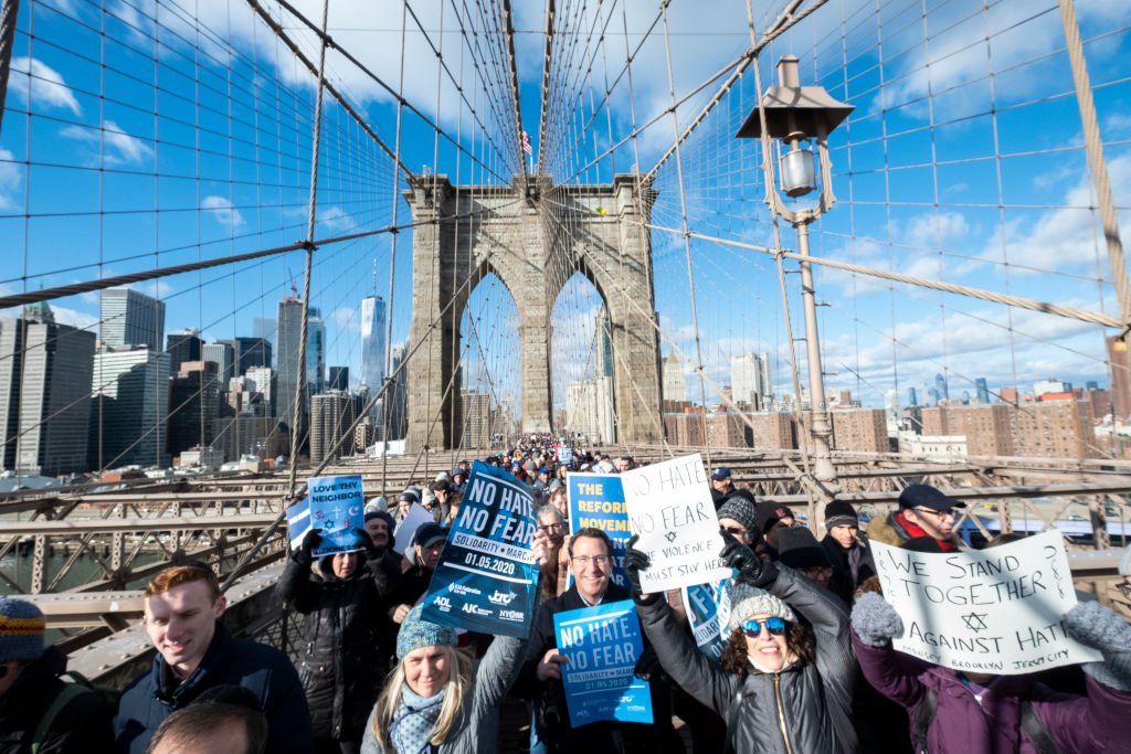 A line of marchers pack the overpass of the Brooklyn Bridge holding signs  that read 'No Hate No Fear' and 'We Stand Together Against Hate' as part of the effort to support the No Hate No Fear Solidarity March against anti-Semitism, January 1, 2020.    (Photo by Ira L. Black/Corbis via Getty Images/ via JTA/SUE)