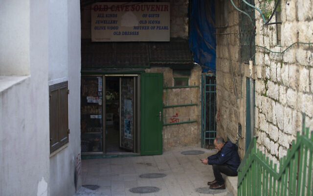 A Palestinian vendor sits in front of his shop near the Church of the Nativity, traditionally believed to be the birthplace of Jesus Christ, in the West Bank City of Bethlehem, November 23, 2020. (AP Photo/Majdi Mohammed)