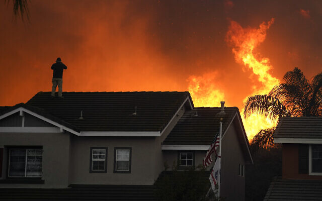 Illustrative: Herman Termeer, 54, stands on the roof of his home as the Blue Ridge Fire burns along the hillside in Chino Hills, California, October 27, 2020. (AP Photo/Jae C. Hong)