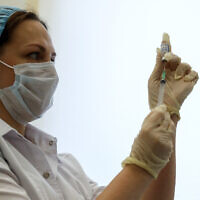 A Russian medical worker prepares a shot of Russia's Sputnik V coronavirus vaccine in Moscow, Russia, December 5, 2020. (AP Photo/Pavel Golovkin)