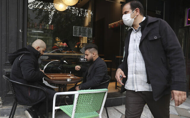 Two men play backgammon outside a cafe as a man wearing a protective face mask to help prevent the spread of the coronavirus walks past, in downtown Tehran, Iran, December 5, 2020. (AP Photo/Vahid Salemi)