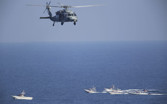 A US MH-60 Seahawk helicopter flies over Iranian Revolutionary Guard patrol boats in the Strait of Hormuz, December 21, 2018. (AP Photo/Jon Gambrell, File)