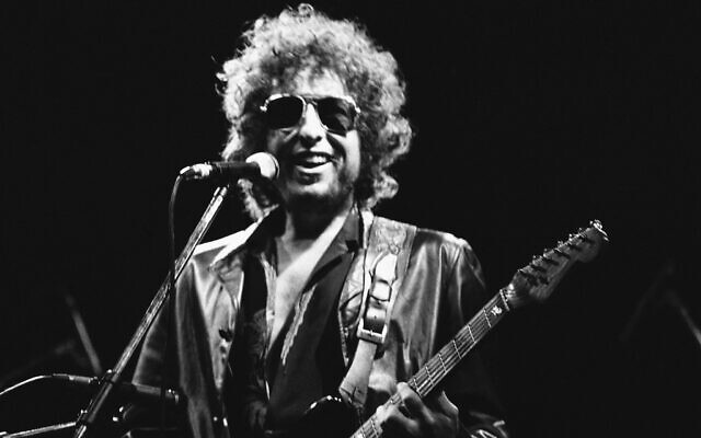 American singer Bob Dylan smiles as he performs during his show at the Colombes Olympic stadium in Colombes, France on June 24, 1981. Dylan's entire catalog of songs, which spans 60 years and is among the most prized next to that of the Beatles, is being acquired by Universal Music Publishing Group. The deal covers 600 song copyrights. (AP Photo/Herve Merliac, File)