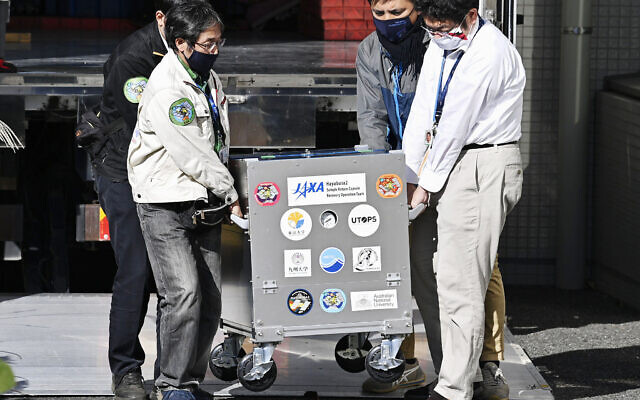 A small capsule dropped by Japan's Hayabusa2 spacecraft, concealed in a container box, arrives at the Japan Aerospace Exploration Agency's research facility in Sagamihara, near Tokyo, December 8, 2020. (Yu Nakajima/Kyodo News via AP)