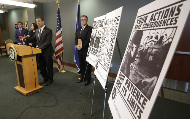 Raymond Duda, FBI Special Agent in Charge in Seattle, speaks during a news conference at a podium, about charges against a group of alleged members of the US neo-Nazi group Atomwaffen Division for cyber-stalking and mailing threatening communications, including the Swastika-laden posters at right, in a campaign against journalists in several cities, February 26, 2020. (AP Photo/Ted S. Warren, File)