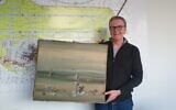 In this photo released by the police department in Duesseldorf on Thursday December 10, 2020, showing Chief Detective Michael Dietz holding a painting from French artist Yves Tanguy.  (Polizei Duesseldorf via AP)