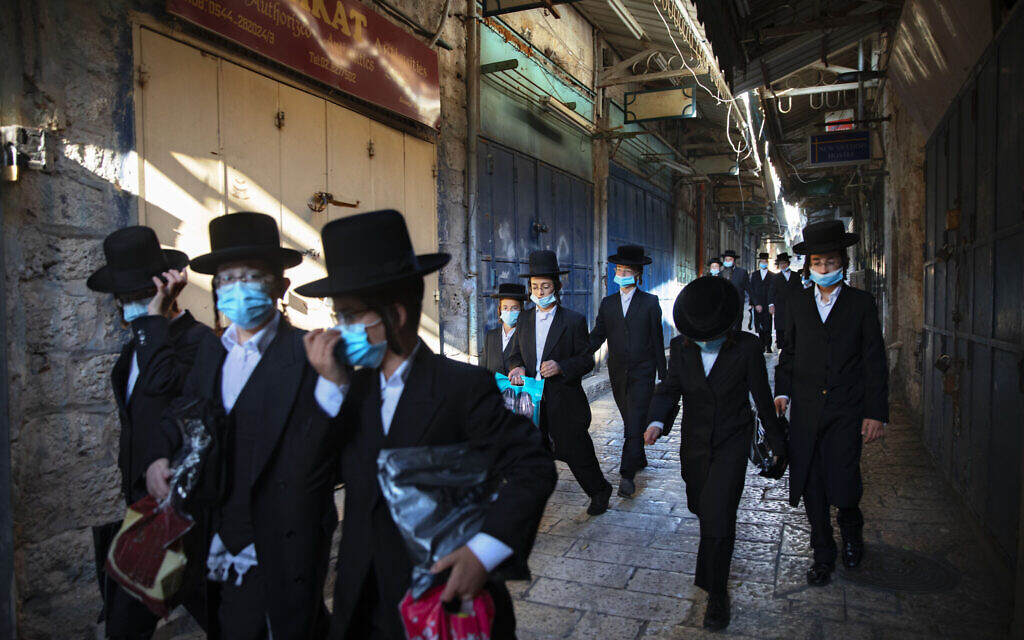 A group of ultra-Orthodox men wear protective face masks following government measures to help stop the spread of the coronavirus, as they walk in Jerusalem's Old City, July 16, 2020. (AP Photo/Oded Balilty)