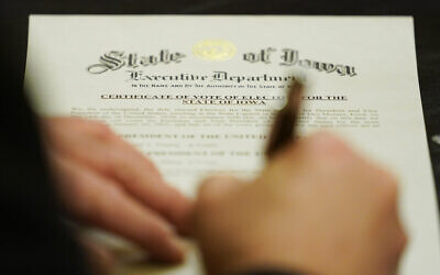 A member of Iowa's Electoral College signs the Certificate of Vote of Electors for the State of Iowa, December 14, 2020, at the Statehouse in Des Moines, Iowa. (AP Photo/Charlie Neibergall)