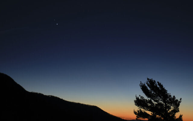 In this December 13, 2020, photo made available by NASA, Saturn, top, and Jupiter, below, are seen after sunset from Shenandoah National Park in Luray, Virginia. (Bill Ingalls/NASA via AP)