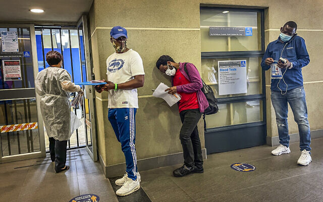 People who were just tested for COVID-19 wait in line to make payment for the test at a private laboratory in Johannesburg, South Africa, December 19, 2020. (AP/Jerome Delay)