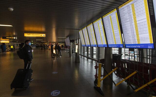 Illustrative: A traveler wearing a face mask checks the flight departures at Schiphol Airport, near Amsterdam, Netherlands. December 18, 2020. (AP Photo/Peter Dejong)