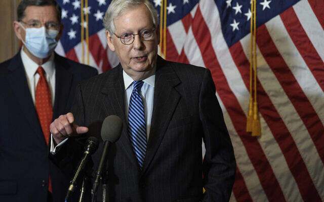 In this Tuesday, Dec. 15, 2020, file photo, Senate Majority Leader Mitch McConnell, of Kentucky, speaks during a news conference with other Senate Republicans on Capitol Hill in Washington, while Sen. John Barrasso, R-Wyoming, listens at left. (Nicholas Kamm/Pool Photo via AP)