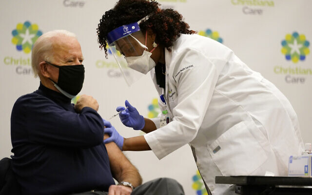 US President-elect Joe Biden receives his first dose of the coronavirus vaccine at ChristianaCare Christiana Hospital in Newark, Delaware on December 21, 2020, from nurse practitioner Tabe Mase. (AP/Carolyn Kaster)