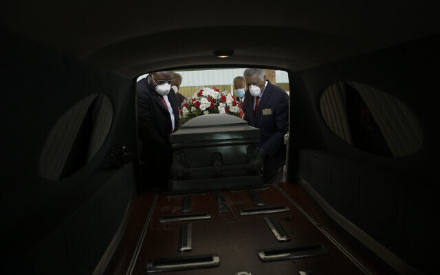 Mortician Cordarial O. Holloway, foreground left, funeral director Robert L. Albritten, foreground right, and funeral attendants Eddie Keith, background left, and Ronald Costello place a casket into a hearse in Dawson, Georgia, April 18, 2020. (AP Photo/Brynn Anderson)