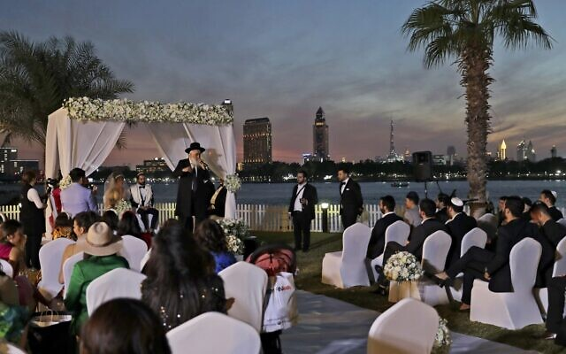 A rabbi officiates under a traditional Jewish wedding canopy during marriage ceremony of the Israeli couple Noemie Azerad, left, seated under the canopy, and Simon David Benhamou, at a hotel in Dubai, United Arab Emirates, December 17, 2020. (Kamran Jebreili/AP)