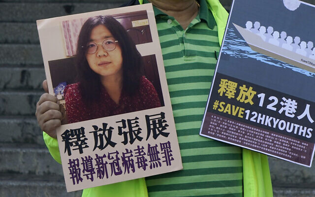 A pro-democracy activist holds placards with the picture of Chinese citizen journalist Zhang Zhan outside the Chinese central government's liaison office, in Hong Kong, Monday, Dec. 28, 2020. Zhang, a former lawyer and citizen journalist from Shanghai, has been sentenced to four years in prison for her reporting on the initial coronavirus outbreak in Wuhan, China. The activists demand the releases of Zhang, as well as the 12 Hong Kong activists detained at sea by Chinese authorities. (AP Photo/Kin Cheung)