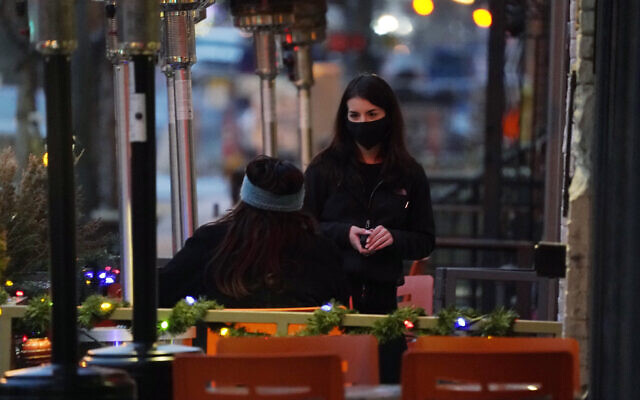 A waitperson wears a face mask while tending to a patron sitting in the outdoor patio of a sushi restaurant, late December 28, 2020, in downtown Denver, Colorado. (AP Photo/David Zalubowski)