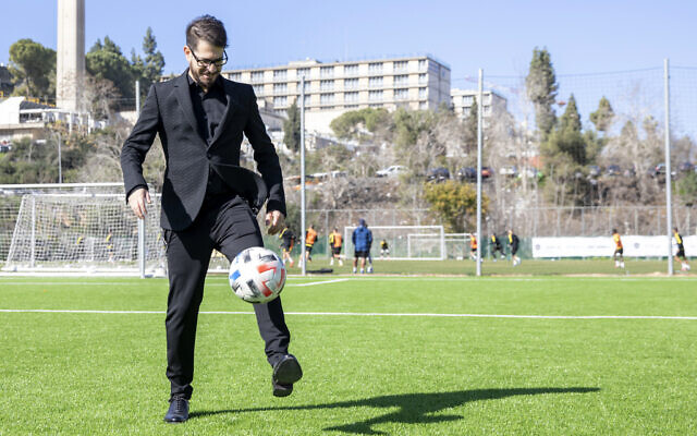 Moshe Hogeg, one of the owners of Beitar Jerusalem FC soccer club, plays with a ball, in the team training ground in Jerusalem, December 27, 2020. (AP Photo/Ariel Schalit)