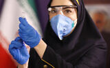 A medic prepares the Coviran coronavirus vaccine produced by Shifa Pharmed, part of a state-owned pharmaceutical conglomerate, for injection at a ceremony in Tehran, Iran, December 29, 2020. (AP Photo/Aref Taherkenareh)