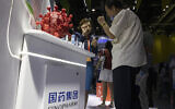 A promoter talks about the COVID-19 vaccine produced by Sinopharm subsidiary CNBG during a trade fair in Beijing on September 6, 2020. (Ng Han Guan/AP)