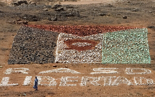 A woman supporting pro-independence Polisario Front rebel soldiers walks near a makeshift Western Sahara flag of painted stones reading: 'Saharawi Arab Democratic Republic, or SADR, free' in the desert near Tifariti, May 20, 2008. (Daniel Ochoa de Olza/AP)