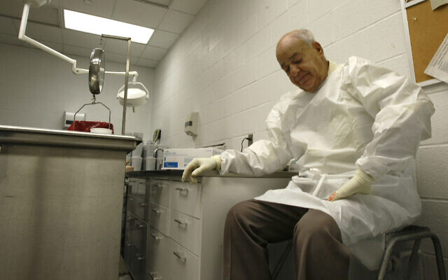 In this July 16, 2009 photo Dr. Cyril Wecht pauses as he records notes during an autopsy in Pittsburgh. (AP Photo/Keith Srakocic)
