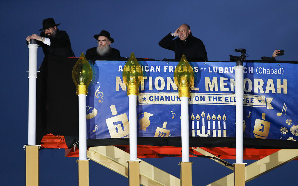 From left, Rabbi Levi Shemtov, with Rabbi Abraham Shemtov and National Economic Director Gary Cohn, struggles in the wind to light the Menorah during the annual National Menorah Lighting, in celebration of Hanukkah, on the Ellipse near the White House in Washington, Tuesday, Dec. 12, 2017. (AP Photo/Carolyn Kaster)