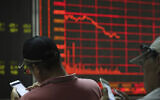 Illustrative: Investors check stock prices on their mobile phones near a display of the stock market index at a brokerage in Beijing on Wednesday, June 12, 2019. (AP/Ng Han Guan)