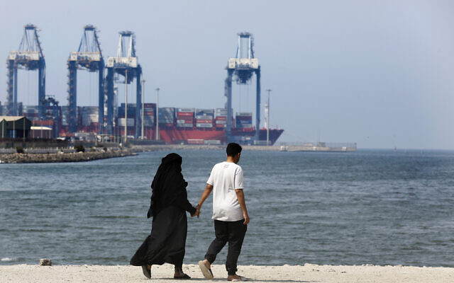 A couple walk in front of the Red Sea port city of Jiddah, Saudi Arabia, Friday, Oct. 11, 2019.  (AP Photo/Amr Nabil)