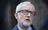 Britain's Labour party leader Jeremy Corbyn speaks to the media on the coronavirus, outside the Finsbury Park Jobcentre, in north London, March 15, 2020. (Hollie Adams/PA via AP)
