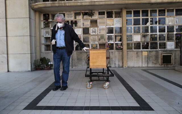 A man pays respects near the coffin of his wife who was 75-years-old, during a funeral ceremony under the care of Paris undertaker Franck Vasseur, at Pere Lachaise cemetery in Paris, April 24, 2020 (AP Photo/Francois Mori)