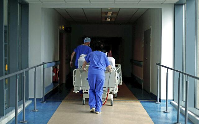 In this May 14, 2020 photo, medical staff transfer a patient through a corridor at the Royal Blackburn Teaching Hospital, in Blackburn, England, amid the coronavirus pandemic. (Hannah McKay/Pool Photo via AP)